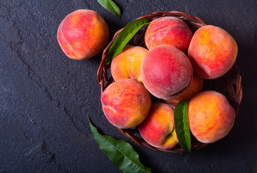 Ripe peaches in basket on stone background